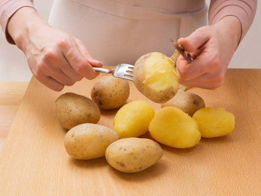 Cooked potatoes being peeled