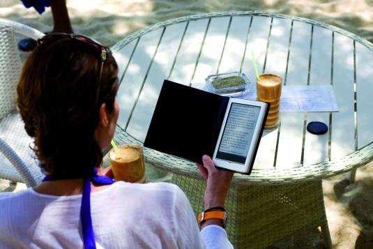 Donna con e-reader in spiaggia