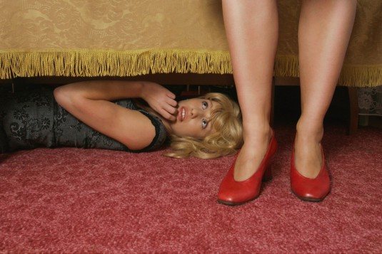 Woman lying under bed