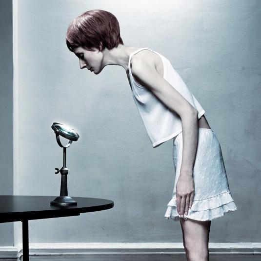 Skinny Woman Looking into Mirror