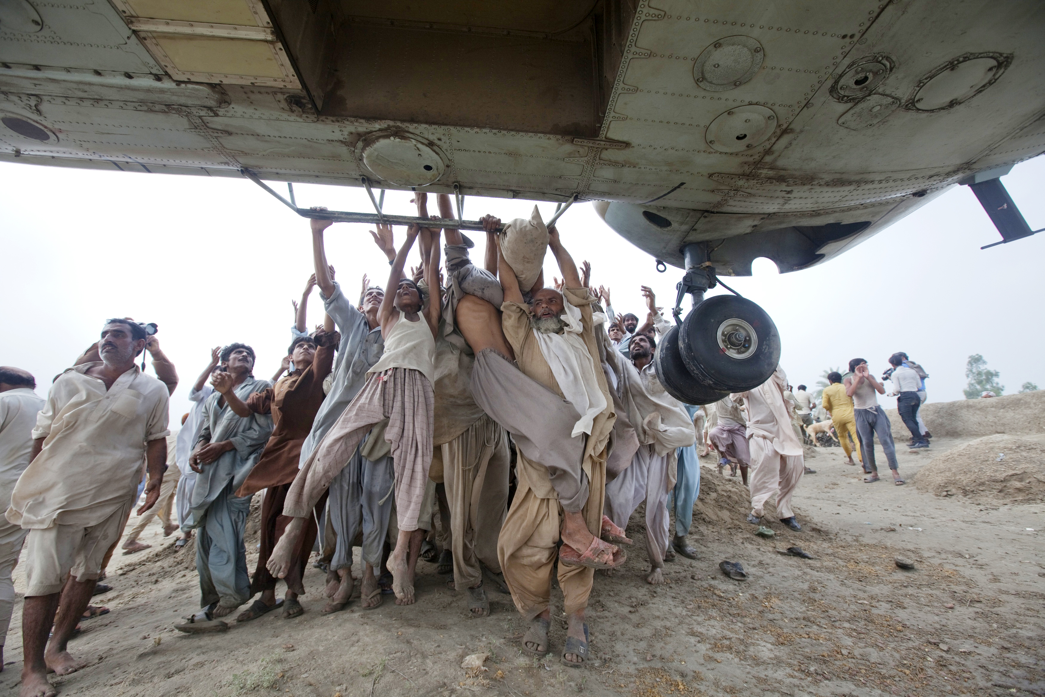 File photo of Marooned flood victims trying to grab the side bars of a hovering Army helicopter which arrived to distribute food supplies in the Muzaffargarh district of Pakistan's Punjab province