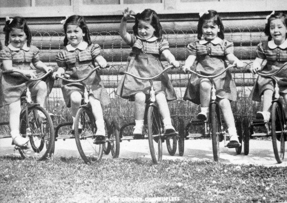 Photograph-of-the-Quints-on-their-tricycles-at-age-four.-566x400